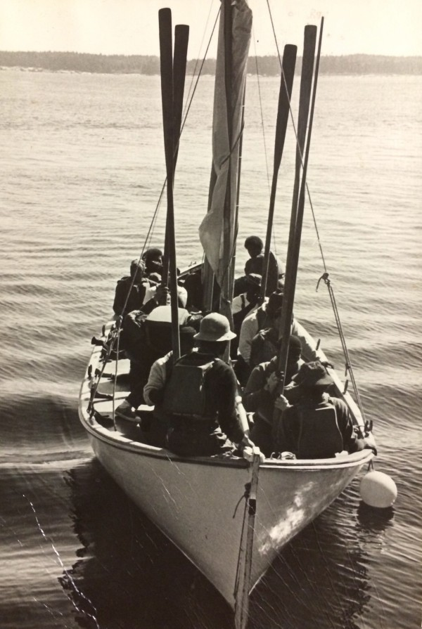 A pulling sailboat full of Hurricane Island Outward Bound students sits at anchor in the 1970s.