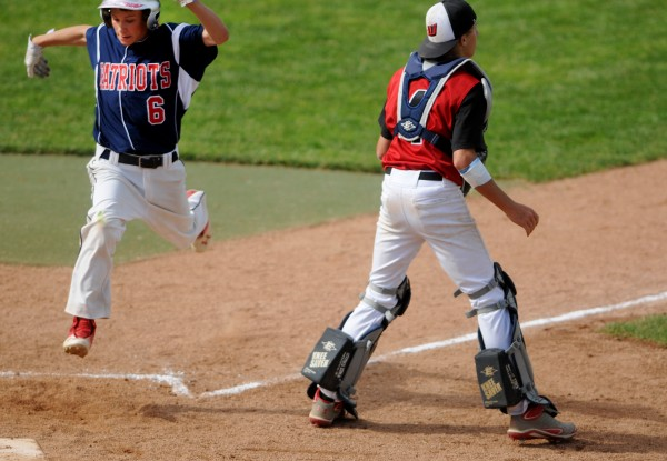 Bangor Christian's Dean Grass crosses home plate for a run past Wiscasset's Grant Hefler in the sixth inning during their Class D baseball state championship game at Mansfield Stadium Saturday in Bangor. Bangor Christian won 5-4 in eight innings.