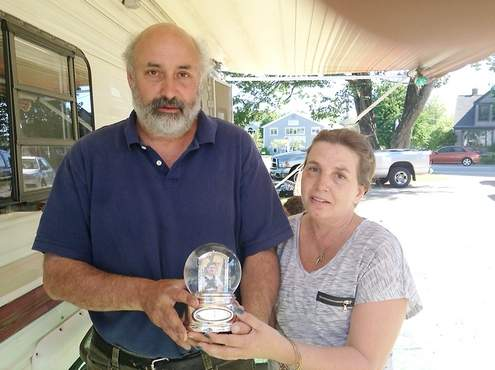 Mike and Kim Gould hold a snow globe that belonged to their late son, Jacob. The snow globe was one of few items salvaged from a fire that destroyed the family's home.