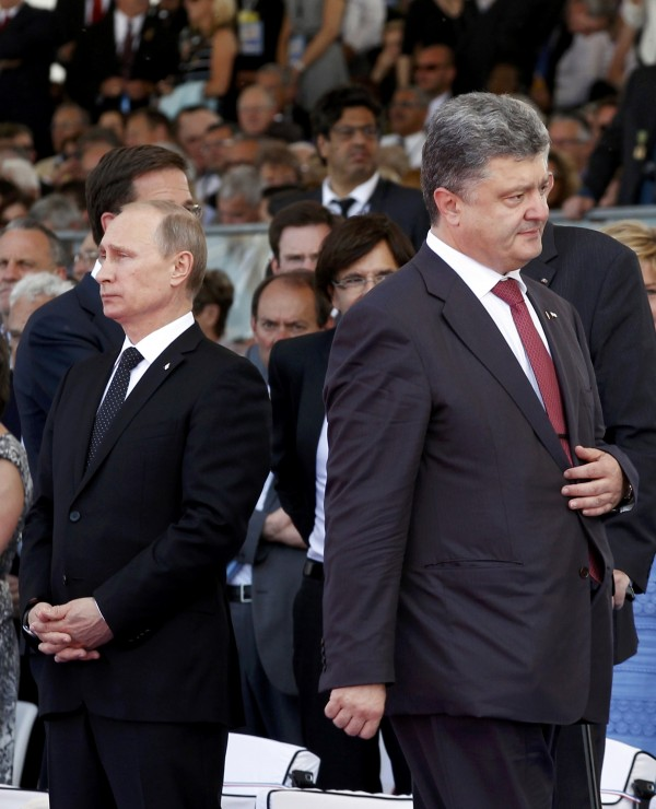 Ukraine's President-elect Petro Poroshenko (R) walks past Russian President Vladimir Putin during the commemoration of the 70th anniversary of the D-Day in Ouistreham, western France, Friday, June 6, 2014.