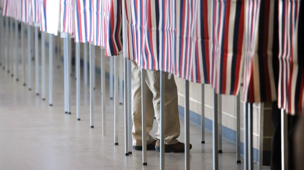 A person stands in a voting booth at the Cross Insurance Center Tuesday morning.