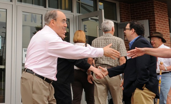 Former state treasurer Bruce Poliquin (left) shakes hands with voters at the Cross Insurance Center in Bangor Tuesday morning.