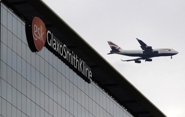 A British Airways airplane flies past a sign for pharmaceutical giant GlaxoSmithKline in London.