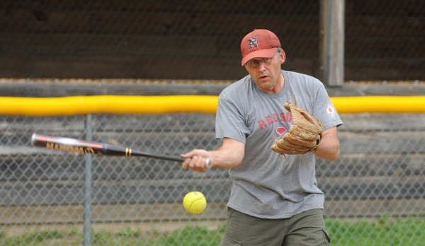 Nokomis High School softball coach J.D. McLellan hits the ball during infield practice in Newport on Monday.
