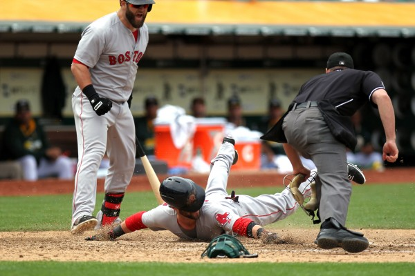 Boston Red Sox first baseman Mike Napoli (12) looks on as second baseman Dustin Pedroia (15) scores on a wild pitch to tie up the game with the Oakland Athletics 1-1 in the eighth inning at O.co Coliseum in Oakland Saturday.