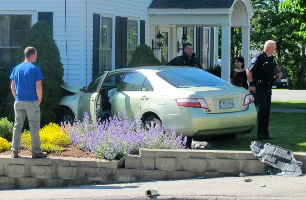A bystander watches as police and firefighters respond to a crash Friday afternoon in Ellsworth. Two cars collided downtown at the intersection of Franklin and Pine streets, sending one of the cars careening into the front of Jordan-Fernald Funeral Home.