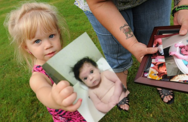 Maddison Foss-Greenaway shows off a picture of her deceased sister Brooklyn, while her mother talks to members of the media at her Clinton home in this August 2012 file photo.