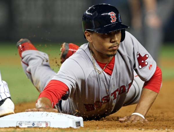 Boston Red Sox right fielder Mookie Betts (50) dives back to first base against the New York Yankees during the sixth inning at Yankee Stadium on Sunday in New York.