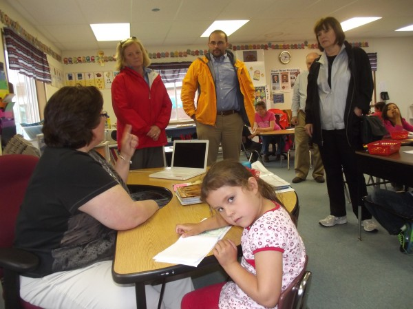 U.S. Rep Chellie Pingree (standing at left) of Maine and U.S. Rep. Betty McCollum (standing at right) of Minnesota listen to kindergarten teacher Martina Fortin (seated) while they tour the Beatrice Rafferty School on the Passamaquoddy Reservation. Also shown is Kyle Molton, a staffer in Pingree's Portland office.