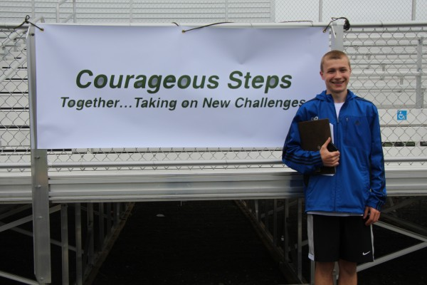 Conner Archer stands next to a sign for a fundraising event he organized, Courageous Steps, at the Victory Field complex on the Old Town High School campus on May 18.