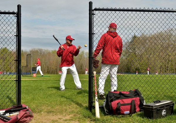Bangor High School head baseball coach Jeff Fahey hits fly balls to his team during warmups before a game against Messalonskee High School in Oakland recently.
