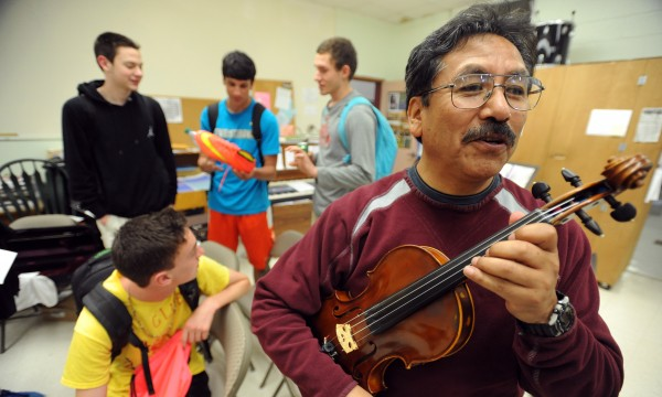 Waldo Caballero (right) is the music teacher and boys soccer coach at Orono High School. Caballero, a conservatory-trained violinist, said that he had to choose between soccer and the instrument in his native Bolivia. He has watched several games with members of the high school soccer team (background) when they had available time in the music room.