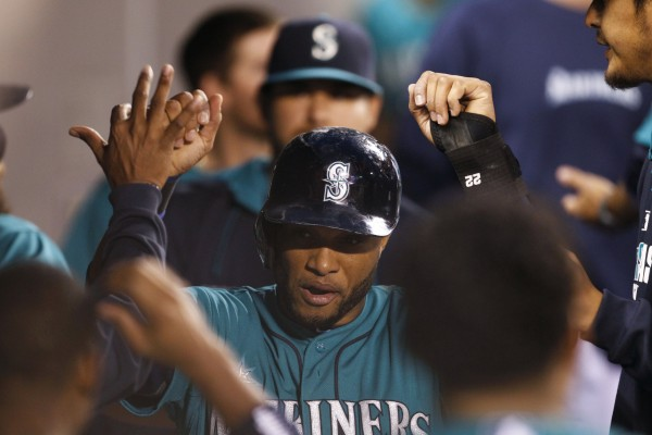 Seattle's Robinson Cano (22) celebrates with teammates in the dugout  after scoring a run against the Boston Red Sox during the seventh inning at Safeco Field in Seattle Monday night.