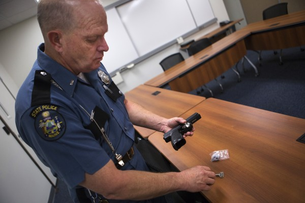 Lt. Wesley Hussey of the Maine State Police shows how to properly put on a trigger lock on Wednesday at the Bangor barracks of the state police.