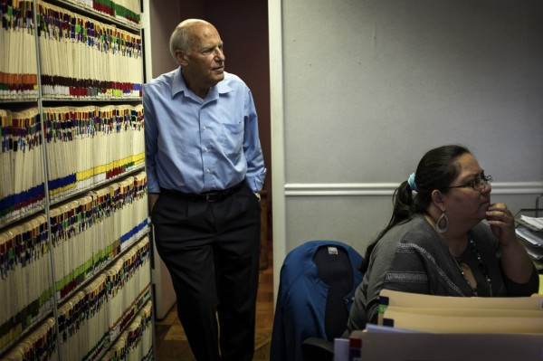 Dr. Gerald Frank leans against reams of neatly organized patient files as he waits with receptionist Dayra Vargas for the after-school rush at his Alexandria, Virginia, office.