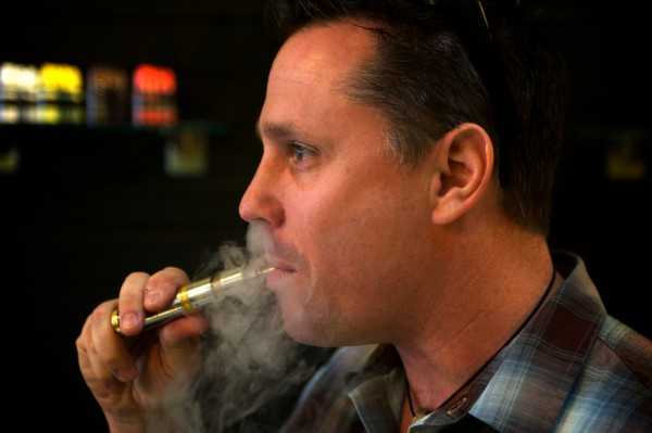 John Kreis, co-owner of the Old Port Vape Shop on Market Street in Portland, enjoys a hit from a personal vaporizer.