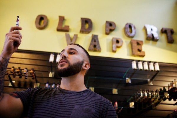Alex Russak, co-owner of Old Port Vape Shop on Market Street in Portland, holds up a sample vial of e-liquid.