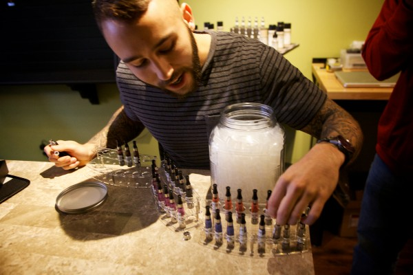 Alex Russak, co-owner of the new Old Port Vape Shop on Market Street in Portland, shows samples of e-liquids customers can try before purchasing.