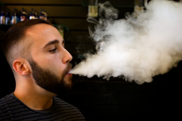 Alex Russek, co-owner of the Old Port Vape Shop on Market Street in Portland, exhales a cloud of vapor.