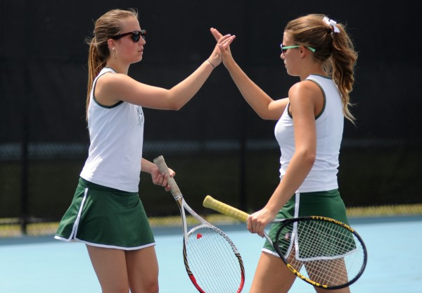 MDI's Mackenzie Myers (left) and Sierra Bloom high-five each other while playing against Waterville's Jayme Saulter and Emma Cristan during Wednesday's Eastern Maine Class B team tennis championship in Waterville.