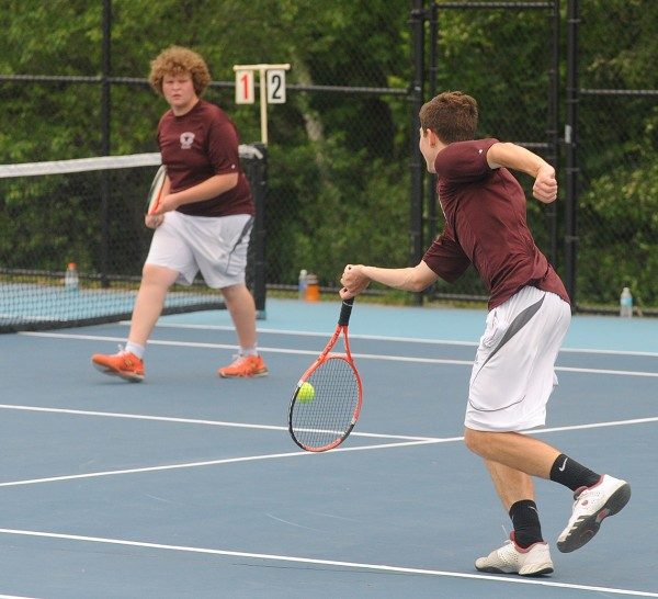 George Stevens Academy's Beowulf Urban (right) makes a return as Tim Dentino looks on during their No. 2 doubles match in the Eastern Maine Class C girls team tennis championships at Colby College in Waterville on Tuesday.