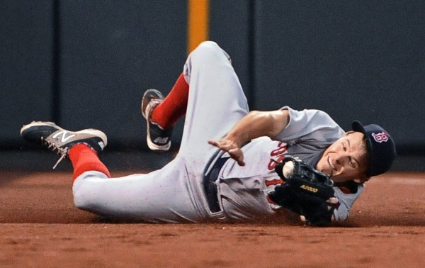 Boston Red Sox left fielder Brock Holt tries to hold on to on a foul ball hit by Baltimore's Chris Davis in the fourth inning of Wednesday night's game at Camden Yards in Baltimore, Maryland. Holt couldn't hold on and the Orioles shut out the Red Sox 6-0.