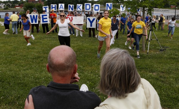 Don (left), a retired Bangor police chief who recently decided to stop treatment for his cancer, and Dora Winslow watch as a flash mob dances and signs are held up on Tuesday at the Bangor Waterfront.