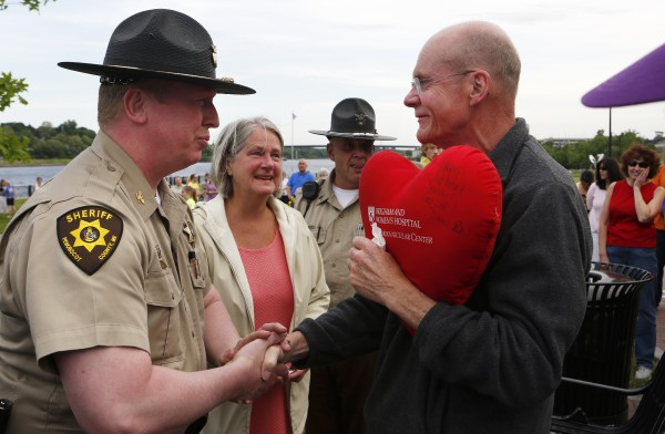 Penobscot County Chief Deputy Sheriff Troy Morton (left) shakes Don Winslow's (right) hand after a flash mob honoring Winslow on Tuesday at the Bangor Waterfront. The community decided to show their support of Don, a retired Bangor police chief, who recently decided to stop treatment on his cancer.