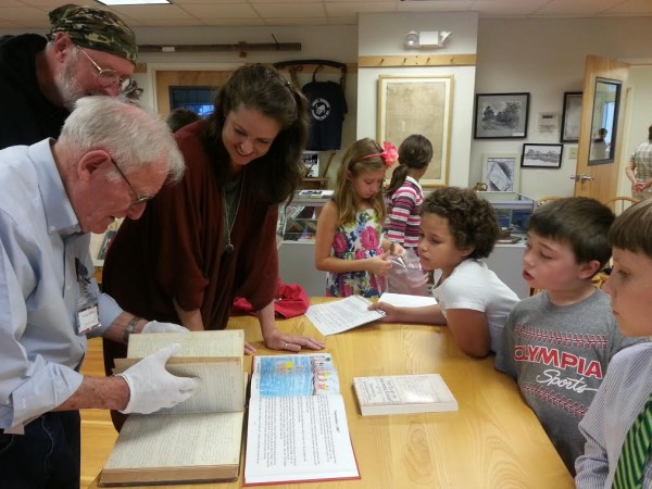 Norman Withee, left, of the Searsmont Historical Society, looks at the original diary of Josephine Knight. Amy Robbins-Wilson, center, transcribed and published the diary, which inspired the third-grade students at Ames Elementary School in Searsmont to illustrate selected entries. On Tuesday, they presented their illustrated diary to the historical society and town. &quotIt's amazing,&quot Withee said.