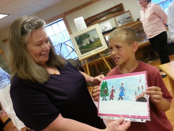 Ames Elementary School third-grade teacher Karen Craig-Foley admires a drawing made by 10-year-old Michael Ham of Morrill. The picture is included in a just-published book that combines student drawings with excerpts from a 19th century schoolteacher's diary.