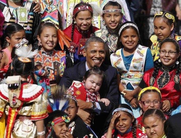 President Barack Obama holds a baby as he poses with children at the Cannon Ball Flag Day Celebration at the Cannon Ball Powwow Grounds on the Standing Rock Sioux  Reservation in North Dakota, on June 13, 2014.