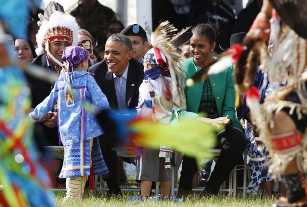 President Barack Obama (center) and first lady Michelle Obama sit next to Chairman of the Standing Rock Sioux Tribe David Archambault II (left) as they attend the Cannon Ball Flag Day celebration at the Cannon Ball Powwow Grounds on the Standing Rock Sioux Reservation in North Dakota, on June 13, 2014.