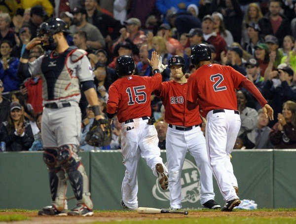 Boston's Dustin Pedroia (15) and Xander Bogaerts (2) are greeted at home plate by Daniel Nava after scoring runs during the third inning against the Cleveland Indians at Fenway Park in Boston Friday night.