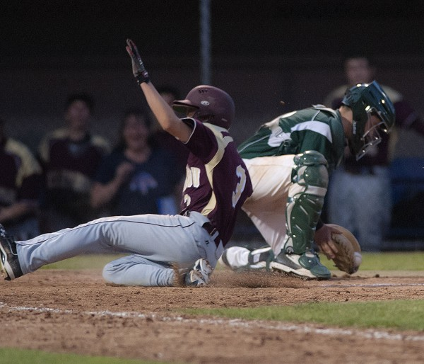 Caribou runner Dustin Bouchard crosses home plate just ahead of the throw in the 10th inning to win the Eastern Maine Class B baseball final over Old Town 4-3 at Mansfield Stadium in Bangor Wednesday night.