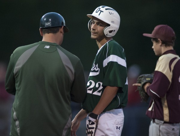 Old Town High School baserunner Eric Hoogterp talks with first base coach Nick Arthers in the 10th inning of their Eastern Maine Class B championship game against Caribou at Mansfield Stadium in Bangor Wednesday night. Caribou won 4-3.