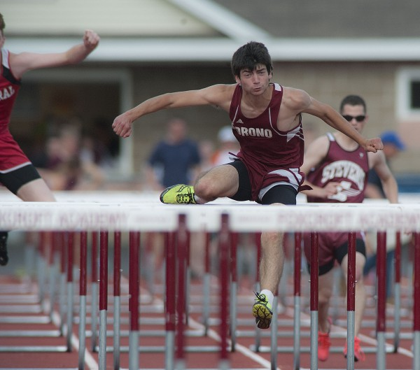 Orono High School hurdler Brandon Crocker cruises to a first-place finish in the boys 100- meter hurdles during the PVC Small School Track and Field Championships in Dover-Foxcroft on Monday.