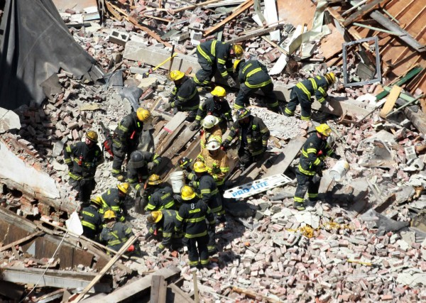 Firemen and rescue workers swarm the site of a building collapse looking for survivors at 22nd and Market Streets in Philadelphia on June 5, 2013.