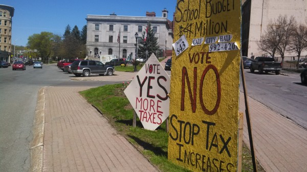 Dueling tax debate signs are seen outside Bangor City Hall recently.