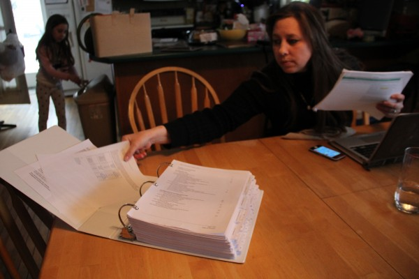 Amy Linscott opens Maine Connections Academy's 536-page application to become an approved charter school in Maine last March. Linscott home-schools her daughters and she hopes to enroll them in the virtual charter school next year.
