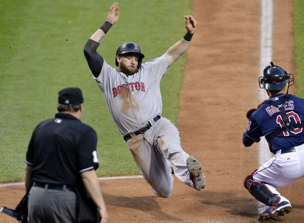 Jonny Gomes of the Boston Red Sox scores past Cleveland Indians catcher Yan Gomes (10) in the sixth inning of Tuesday night's game at Progressive Field. The Indians won 5-3.