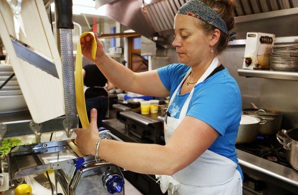Aragosta owner and head chef Devin Finigan works pasta through a pasta machine to create her signature dish, lobster ravioli recently in Stonington.