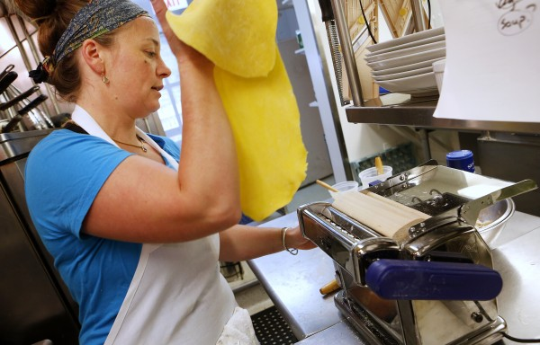 Aragosta owner and head chef Devin Finigan works pasta through a pasta machine to create her signature dish, lobster ravioli, recently in Stonington.
