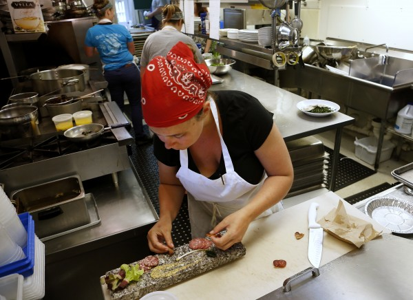 Aragosta line cook Susannah Taylor works to plate a meat board recently in Stonington. Aragosta cures all of their meats for the board.