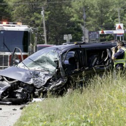A Maine State Police officer takes photographs of a mini van involved in a two car, head-on collision on Route 202 in North Monmouth late Friday morning. The female driver was taken to Central Maine Medical Center with serious injuries.
