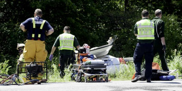 Emergency personnel work near a white Lincoln in the ditch of Route 202 in North Monmouth Friday morning that was involved in a two car, head-on collision in front of TJ's Pizzeria. The male driver was the car was pronounced dead at the scene.