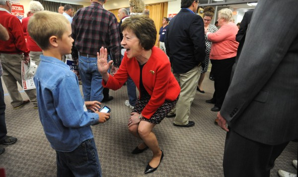 U.S. Sen. Susan Collins high-fives Isaiah Dunphy, 9, during a rally for Republican politicians who are running for re-election or office at Husson University in Bangor Friday morning.