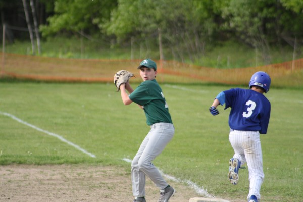 First baseman Reece Carter gets the out at first and looks to home to turn a double play.