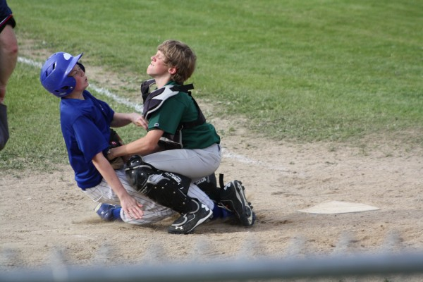 Catcher Brad McKechnie puts on the tag and holds on to the ball to complete the double play.