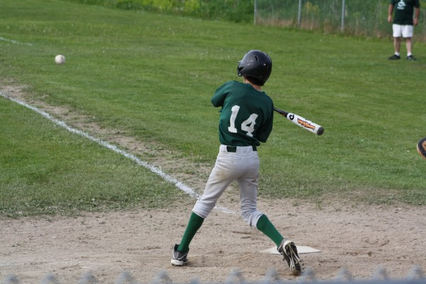 Grant Kidon  zeroes in on the pitch and hits a double.
