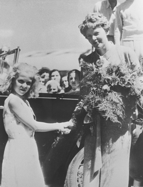 1934: Amelia Earhart shakes hands with a young Joanne Jordan, former chairperson of the Bangor Publishing Co. board of directors,  at the Bangor Airport.